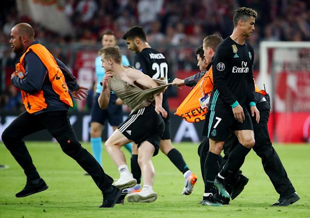 Soccer Football - Champions League Semi Final First Leg - Bayern Munich vs Real Madrid - Allianz Arena, Munich, Germany - April 25, 2018 Stewards chase a pitch invader as he runs past Real Madrid's Cristiano Ronaldo after the match REUTERS/Michael Dalder