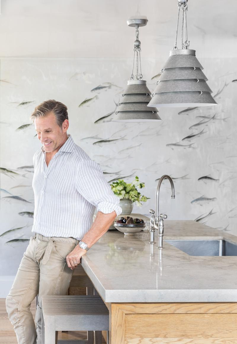 Marks in his kitchen with two Surfrider pendants hanging above him.