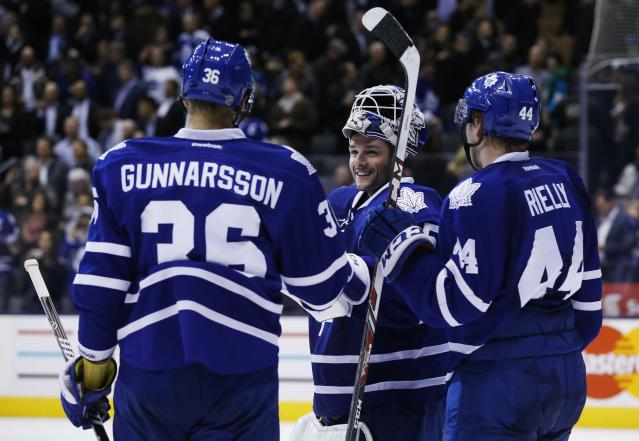 Toronto Maple Leafs' Carl Gunnarsson, Jonathan Bernier, and Morgan Rielly celebrate defeating the New York Islanders in an NHL hockey hockey game, Tuesday, Nov. 19, 2013 in Toronto. (AP Photo/The Canadian Press, Mark Blinch)