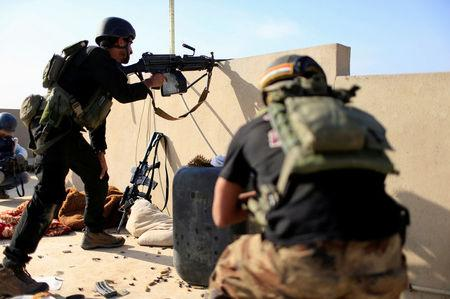 Member of the Iraqi Counter Terrorism Service fies his weapon at Islamic State militants in the al-Zahraa neighborhood of Mosul, Iraq