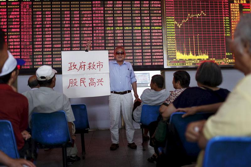 """An investor holds a board showing """"government saves the market so that investors will be happy"""" at a brokerage house in Shanghai"""