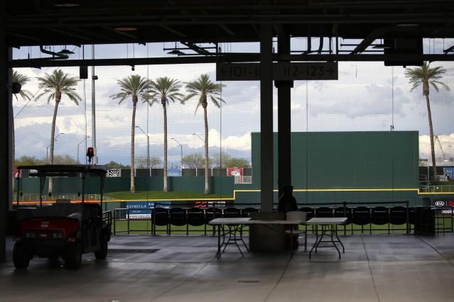 A closed Goodyear Ballpark, spring training home of the Cleveland Indians and Cincinnati Reds baseball teams, is empty Thursday, March 12, 2020, in Goodyear, Ariz. Major League Baseball has suspended the rest of its spring training game schedule because if the coronavirus outbreak. MLB is also delaying the start of its regular season by at least two weeks. (AP Photo/Ross D. Franklin)