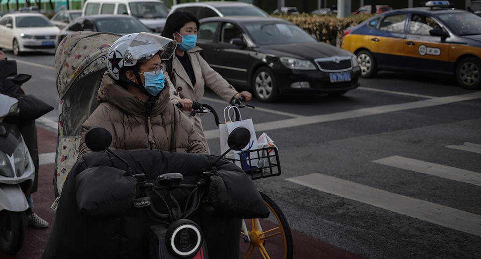 Two people wearing face masks riding their bikes during the coronavirus pandemic in Beijing.