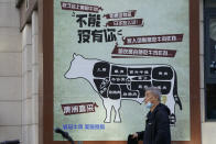 A man carries his meal past an advertisement promoting imported beef from Australia in Beijing, Monday, Nov. 23, 2020. China has stirred controversy with claims it has detected the coronavirus on packages of imported frozen food. (AP Photo/Ng Han Guan)