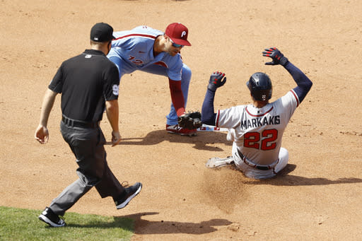 Atlanta Braves' Nick Markakis, right, is tagged out by Philadelphia Phillies second baseman Neil Walker after trying to steal second during the fourth inning of the first baseball game in a doubleheader, Sunday, Aug. 9, 2020, in Philadelphia. (AP Photo/Matt Slocum)