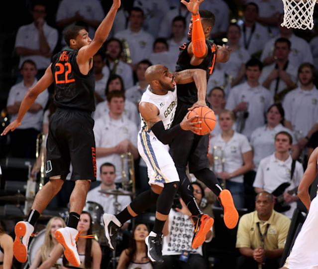 Georgia Tech guard Trae Golden, center, attempts a shot as Miami forwards Donnavan Kirk, left, and Raphael Akpejiori, right, defend in the first half of an NCAA college basketball game, Saturday, Jan. 18, 2014, in Atlanta. Golden was fouled on the play. (AP Photo/Jason Getz)