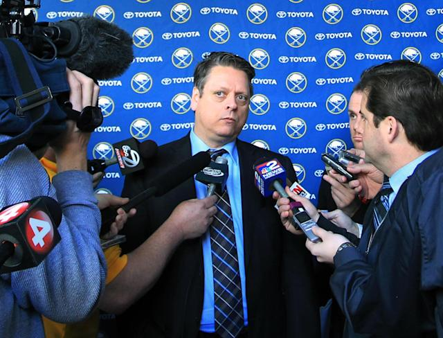 Tim Murray, center, the new Buffalo Sabres hockey team general manager, takes questions from the media at the First Niagara Center in Buffalo, N.Y. , Thursday, Jan. 9, 2014. (AP Photo/Nick LoVerde)