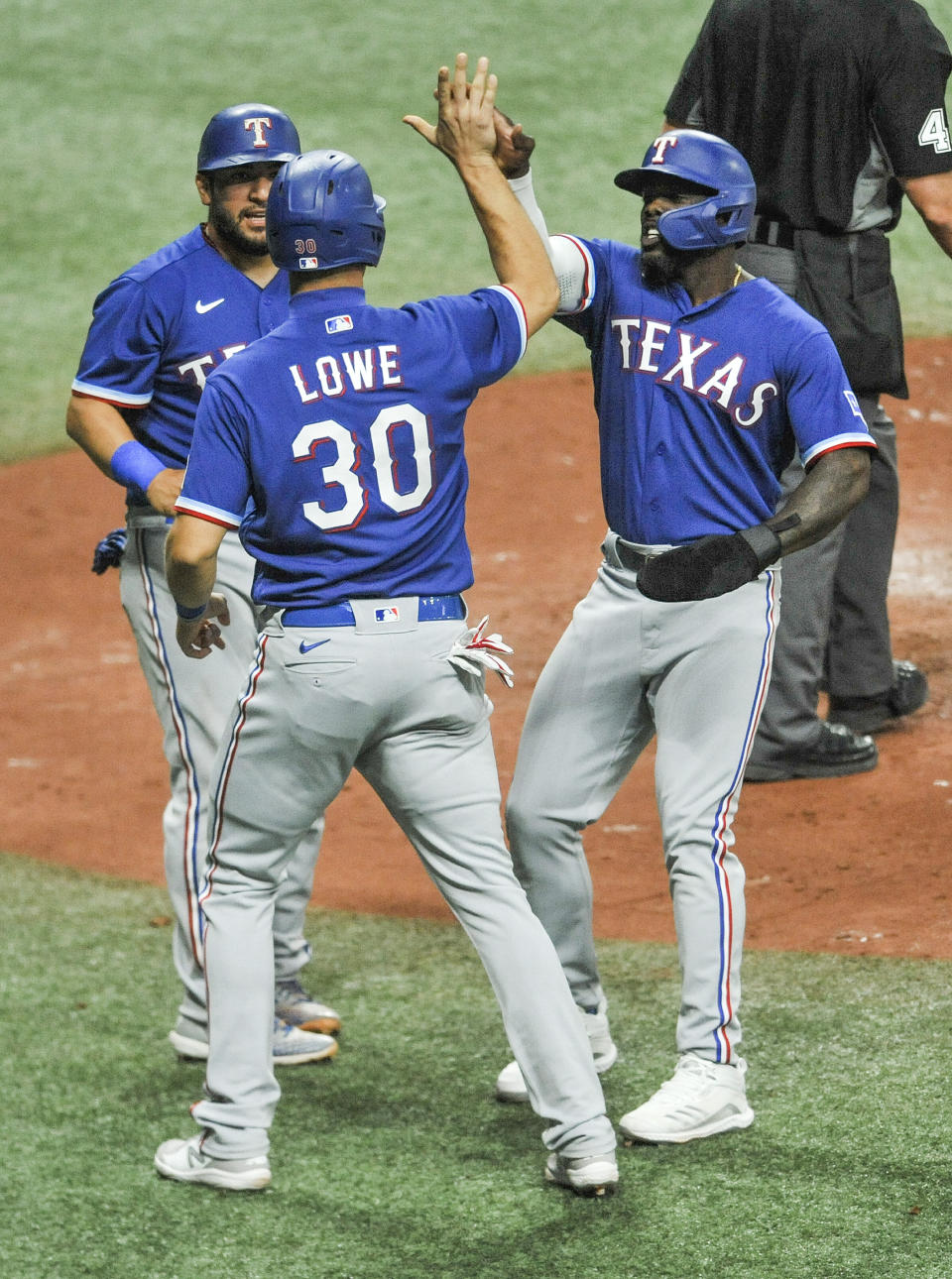 Texas Rangers' Jose Trevino, left, Nate Lowe (30) and Adolis Garcia celebrate after scoring on Nick Solak's bases-loads double off Tampa Bay Rays' Ryan Yarbrough during the fourth inning of a baseball game Tuesday, April 13, 2021, in St. Petersburg, Fla. (AP Photo/Steve Nesius)