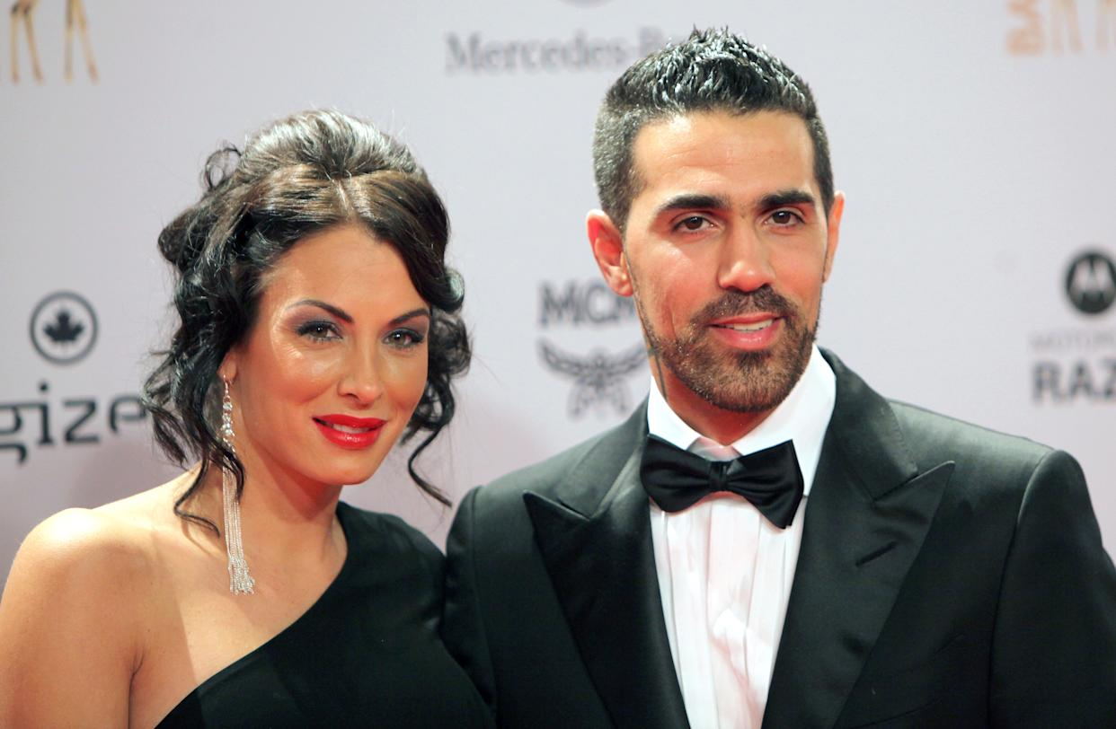 (FILES) In this file photo taken on November 10, 2011 German-Tunisian rap singer Bushido (R) poses with his partner Anna Maria Lagerblom, now called Anna-Maria Ferchichi, as they arrive for the Bambi awards ceremony in Wiesbaden, Germany. - Berlin crime gangs of Arab origin have long earned infamy with gang violence and brazen robberies but now, police warn, they have targeted a new generation of refugees for recruitment. Germany's best-known rapper, Bushido, long boasted about his close ties to one Berlin clan -- until they had a falling out this year and he sought the protection of a rival group. (Photo by DANIEL ROLAND / AFP) / Germany OUT / TO GO WITH AFP STORY BY YANNICK PASQUET AND FRANK ZELLER        (Photo credit should read DANIEL ROLAND/AFP via Getty Images)