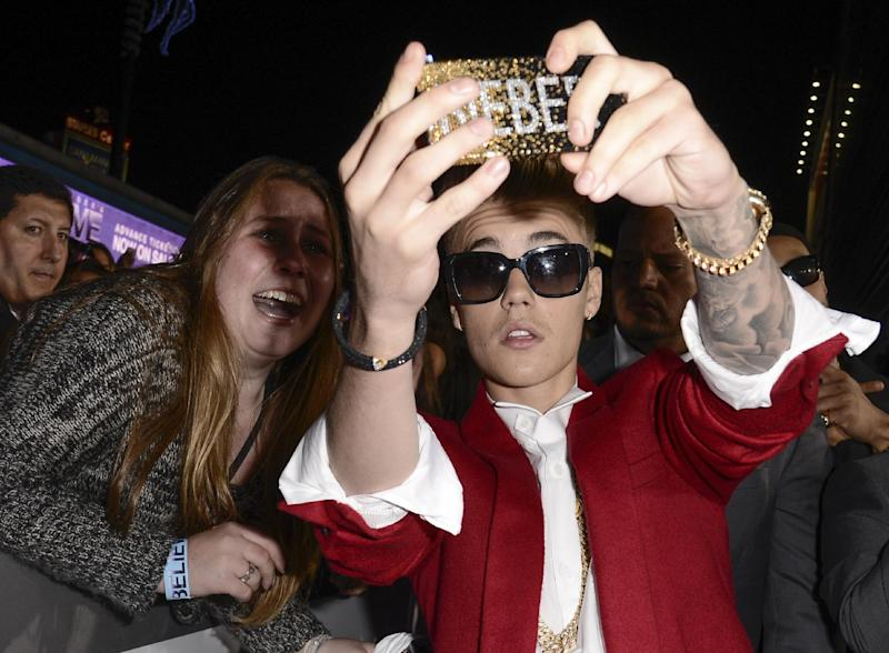 """File- In this Dec. 18, 2013 file photo, singer Justin Bieber takes a """"selfie"""" with a fan at a premiere in Los Angeles. The Los Angeles Sheriff's Department says it is searching Justin Bieber's home for evidence in an egg-tossing vandalism case involving the pop star on Thursday, Jan. 9, 2014. (AP Photo/Dan Steinberg, Invision)"""
