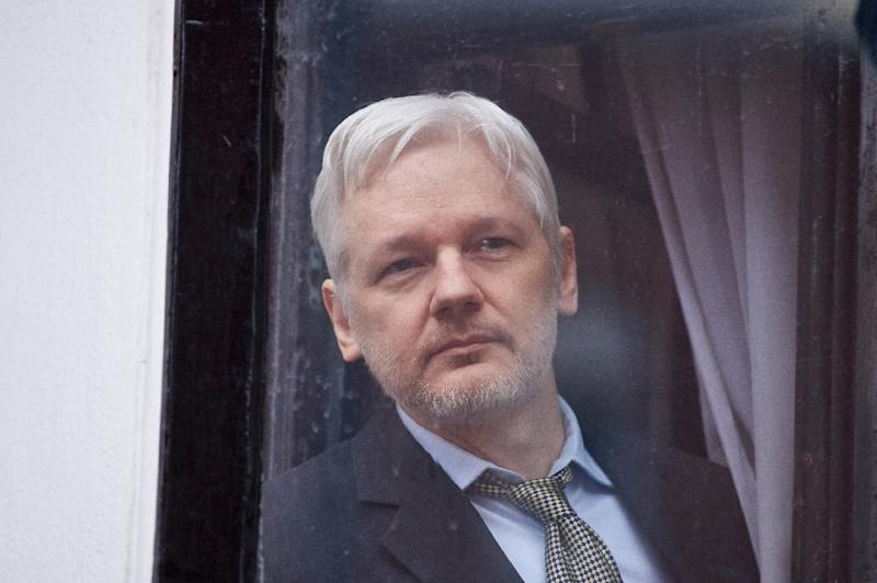 WikiLeaks founder Julian Assange is seen through the window of the door leading to the balcony of the Ecuadorian embassy in central London on February 5, 2016