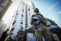 Armed soldiers stand guard outside Pangsapuri Permai, residential area placed under the enhanced movement control order (EMCO) due to drastic increase in the number of COVID-19 cases recorded over the past 10 days in Cheras, outskirt of Kuala Lumpur, Malaysia, Friday, May 28, 2021. Malaysia's latest coronavirus surge has been taking a turn for the worse as surging numbers and deaths have caused alarm among health officials, while cemeteries in the capital are dealing with an increasing number of deaths. (AP Photo/Vincent Thian)