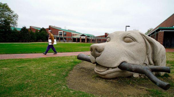 PHOTO: FILE - In this March 24, 2020 file photo, a woman walks past a dog sculpture on the campus of the North Carolina State University College of Veterinary Medicine in Raleigh, N.C. (Allen G. Breed/AP)