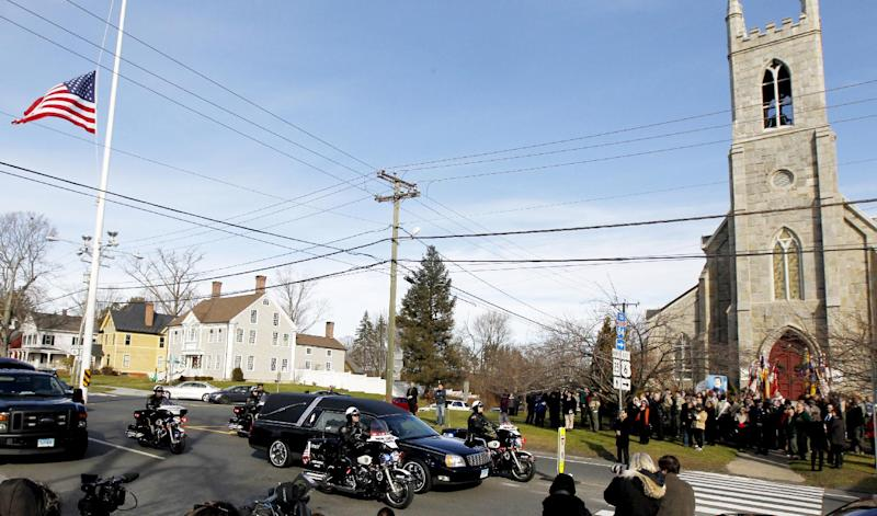 While mourners gather outside of Trinity Episcopal Church, right, during funeral services for Benjamin Andrew Wheeler, one of the students killed in the Sandy Hook Elementary School shooting last week, a hearse with another shooting victim rides through during a procession, Thursday, Dec. 20, 2012, in Newtown, Conn. The victims died when the gunman, Adam Lanza, walked into Sandy Hook Elementary School in Newtown,  Dec. 14, and opened fire, killing 26 people, including 20 children, before killing himself. (AP Photo/Julio Cortez)