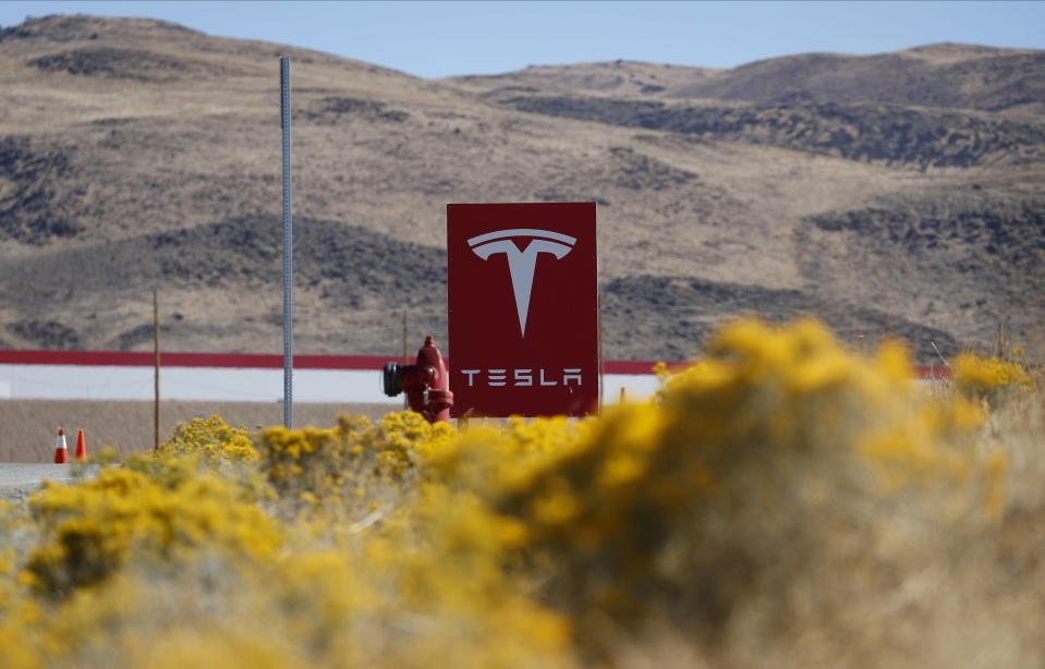 FILE - In this Oct. 13, 2018, file photo, a sign marks the entrance to the Tesla Gigafactory in Sparks, Nev. A Russian man was sentenced Monday, May 24, 2021, to what amounted to time already served in U.S government custody and to be deported for trying to pay a Tesla employee $500,000 to install computer malware in a bid to steal company secrets for ransom. Egor Kriuchkov apologized to a federal judge in Reno who acknowledged the attempted hack wasn't successful and the company network wasn't compromised. (AP Photo/John Locher, File)