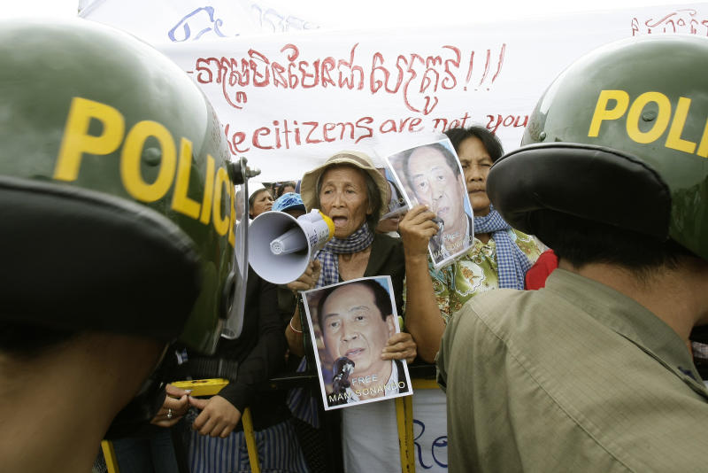 Cambodian supporters of Mam Sonando, one of Cambodia's most prominent human rights defenders, protest in front of the Phnom Penh Municipal Court, in Phnom Penh, Cambodia, Monday, Oct. 1, 2012. Some 300 supporters gathered to demand the release of local radio station owner Mam Sonando, who is accused of leading a secession and has been held in pre-trial detention for almost two months. His verdict is scheduled to be announced at the court on Monday. (AP Photo/Heng Sinith)