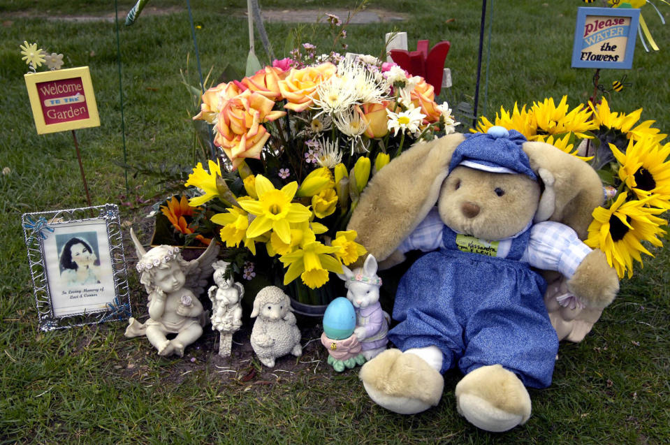 FILE - In this Thursday, March 17, 2005, file photo, The gravesite of Laci and Conner Peterson is adorned with flowers and stuffed animals at Burwood Cemetery in Escalon, Calif. A California district attorney won't seek a new death sentence against Scott Peterson, convicted in 2005 of murdering his pregnant wife Laci. In a filing Friday, May 28, 2021, the Stanislaus County district attorney's office said it would drop efforts to restore the penalty thrown out last year by the state Supreme Court. (AP Photo/Al Golub, File)