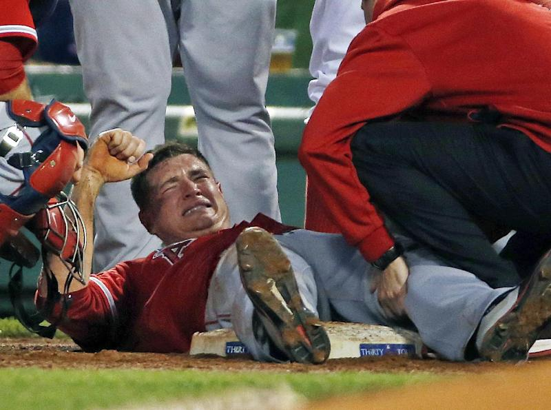 Los Angeles Angels starting pitcher Garrett Richards grimaces as he is attended to on the field after an injury during the second inning of a baseball game against the Boston Red Sox at Fenway Park in Boston, Wednesday, Aug. 20, 2014. (AP Photo/Elise Amendola)