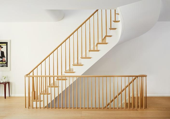 The softly curving staircase leads to the upper level: The flooring is custom-made wide plank whitewashed white oak by State of the Art Wood Floor Gallery.