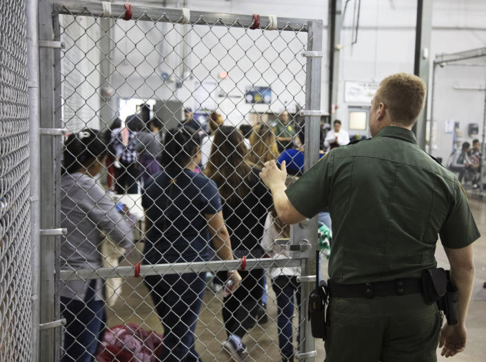<p>A U.S. Border Patrol agent watches as people who've been taken into custody related to cases of illegal entry into the United States, stand in line at a facility in McAllen, Texas, Sunday, June 17, 2018. (Photo: U.S. Customs and Border Protection's Rio Grande Valley Sector via AP) </p>