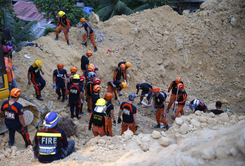 Rescuers dig through the rubble to search for possible survivors following a landslide that buried dozens of homes in Naga city, Cebu province central Philippines on Thursday Sept. 20, 2018. A landslide set off by heavy rains buried homes under part of a mountainside in the central Philippines on Thursday, and several people are feared buried, including two who sent text messages seeking help. (AP Photo/Bullit Marquez)