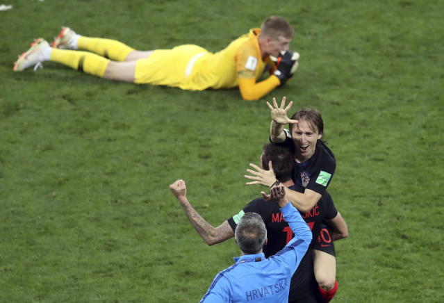 Croatia's Luka Modric, right, celebrates next to England goalkeeper Jordan Pickford, on the ground, at the end of the semifinal match between Croatia and England at the 2018 soccer World Cup in the Luzhniki Stadium in Moscow, Russia, Wednesday, July 11, 2018. (AP Photo/Thanassis Stavrakis)