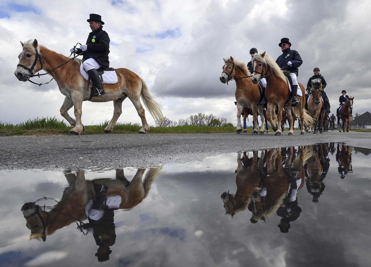 <p>Men riding decorated horses are mirrored in a puddle during the traditional Easter procession of Sorbs in Klein Radden, eastern Germany, Sunday, April 16, 2017. Sorbian men wearing black coats and top hats, sing holy songs on horseback and preach the message of Jesus' resurrection.The Sorbs are a Slavic, Catholic minority group in eastern Germany. (Patrick Pleul/dpa via AP) </p>