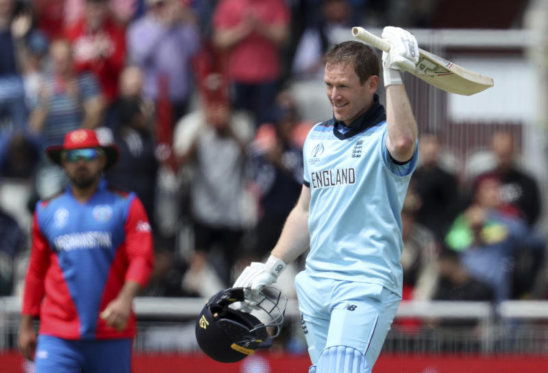 England's captain Eoin Morgan raises his bat to celebrate scoring a century during the Cricket World Cup match between England and Afghanistan at Old Trafford in Manchester, England, Tuesday, June 18, 2019. (AP Photo/Rui Vieira)