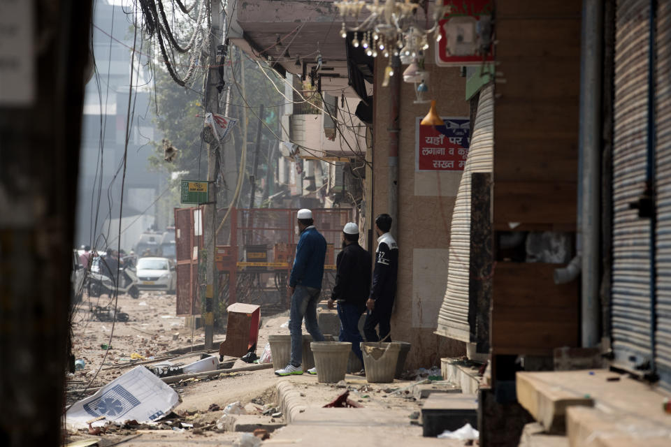 A group of Muslims stand on a street that saw violence on Tuesday in New Delhi, India, Wednesday, Feb. 26, 2020. At least 20 people were killed in three days of clashes in New Delhi, with the death toll expected to rise as hospitals were overflowed with dozens of injured people, authorities said Wednesday. The clashes between Hindu mobs and Muslims protesting a contentious new citizenship law that fast-tracks naturalization for foreign-born religious minorities of all major faiths in South Asia except Islam escalated Tuesday. (AP Photo/Rajesh Kumar Singh)