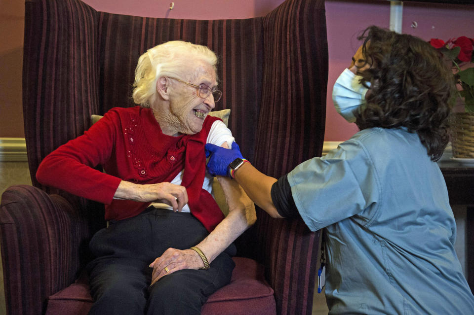 Ellen Prosser, known as Nell, who is 100 years old, receives the Oxford/AstraZeneca COVID-19 vaccine from Dr Nikki Kanani at the Sunrise Care Home in London, as the government continues to ramp up the vaccination program. (Kirsty O'Connor/Pool Photo via AP)