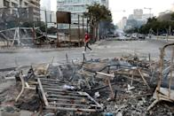 A man walks past debris at a site of protest that happened yesterday over deteriorating economic situation in Beirut