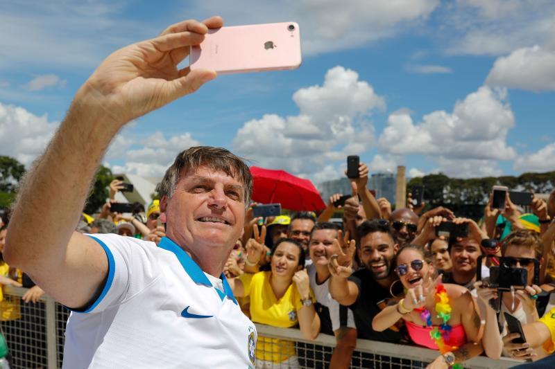 Brazilian President Jair Bolsonaro takes a selfie with supporters in front of the Planalto Palace, after a protest against the National Congress and the Supreme Court, in Brasilia, on March 15, 2020. (Photo by Sergio LIMA / AFP) (Photo by SERGIO LIMA/AFP via Getty Images)