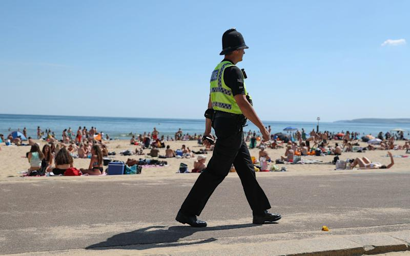 A police officer patrols along the beach in Bournemouth, Dorset, as the public are being reminded to practice social distancing following the relaxation of the coronavirus lockdown restrictions in England -Two-metre social distancing rule based on outdated science that may have overestimated coronavirus risk by up to fifteen times - PA