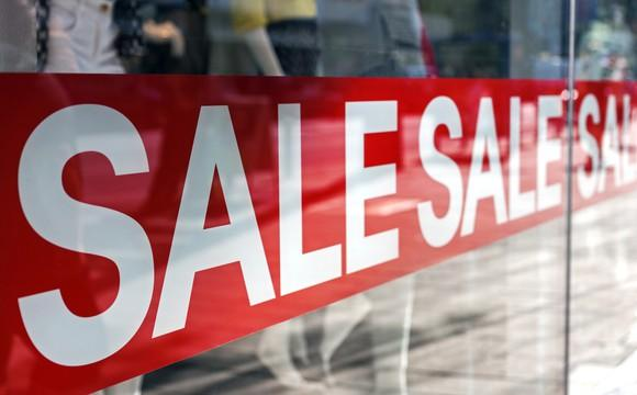 A red sale sign posted on a glass storefront window.