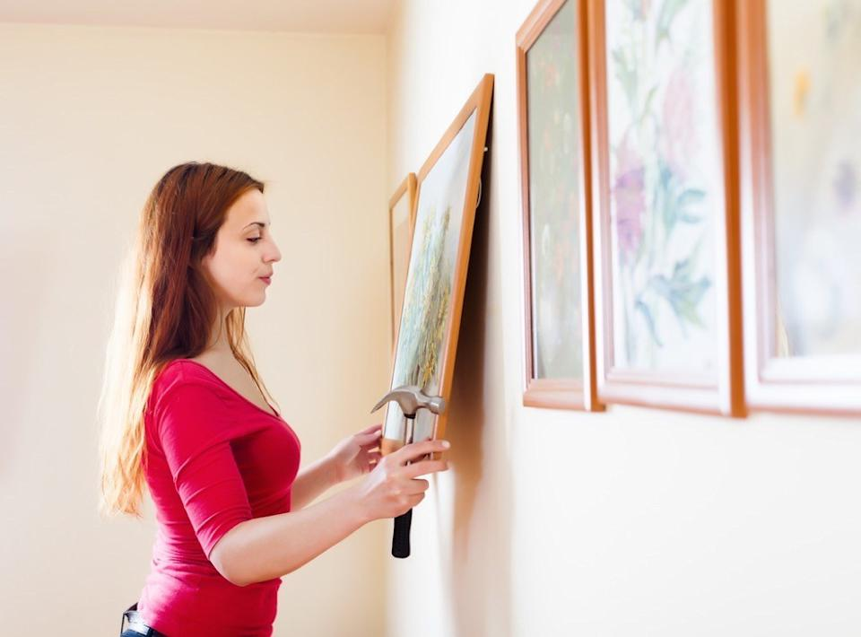 woman hanging painting on wall, home upgrades