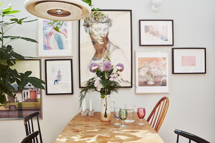 "<div class=""caption""> A smattering of artwork hangs above Rosie's dining table. She isn't embarrassed to confess that the California image is just the picture that came in the IKEA frame. </div>"