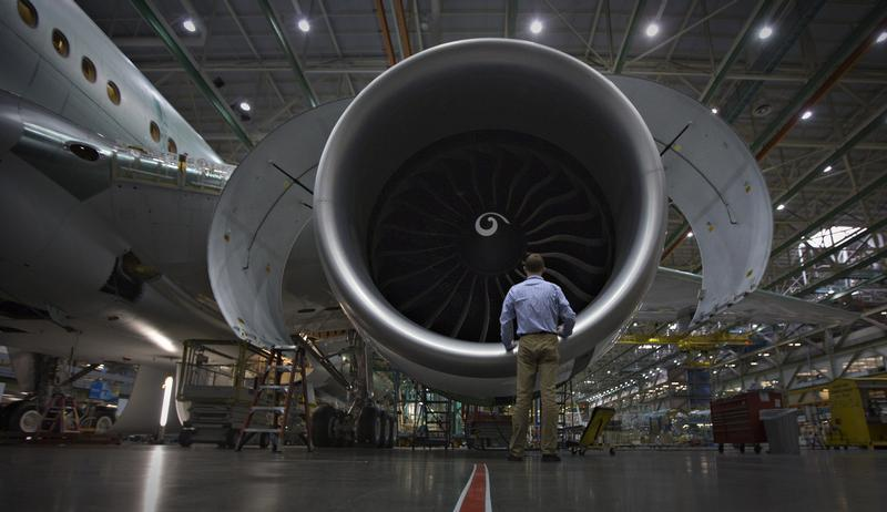 A worker stands in front of an engine on the Boeing 777 at their assembly operations in Everett