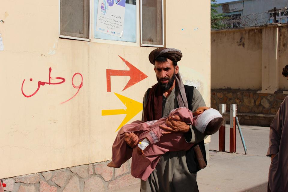 An Afghan civilian carry a wounded child to the hospital after he was injured during fighting between Taliban and government in Badghis province, northwest of Afghanistan (AP)