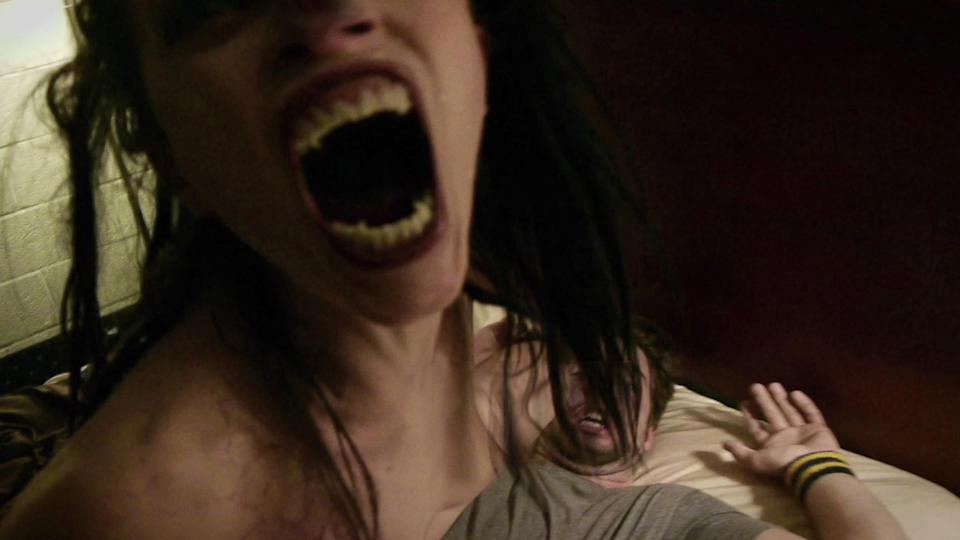 A still from VHS Amateur Night shows a woman with sharp teeth opening her mouth above a screaming man