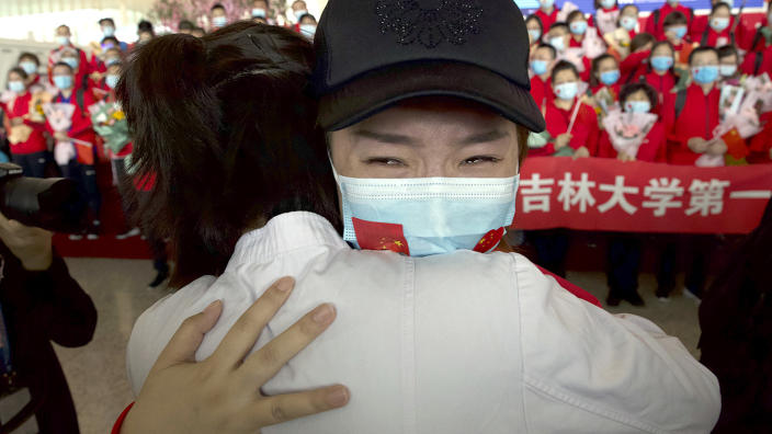 A medical worker from China's Jilin Province reacts as she prepares to return home at Wuhan Tianhe International Airport in Wuhan in central China's Hubei Province, Wednesday, April 8, 2020.  (Ng Han Guan/AP)