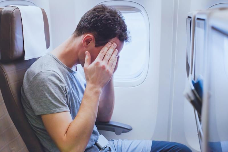 Headache in the airplane, man passenger afraid and feeling bad during the flight in plane.