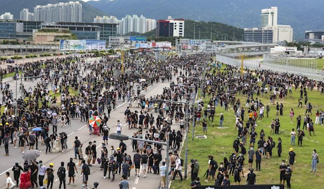 Travellers and airline crew were forced to get off their buses and make their way to the airport on foot as protesters crippled airport services on September 1. Photo: Felix Wong