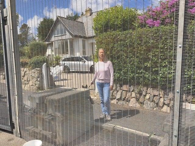 Christine Norton behind security fencing installed across Crabis Bay and St Ives (Colin Drury)