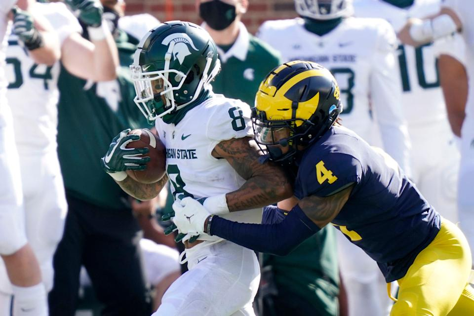 Michigan State wide receiver Jalen Nailor is tackled by Michigan defensive back Vincent Gray after a catch during the first half on Saturday, Oct. 31, 2020, at Michigan Stadium.