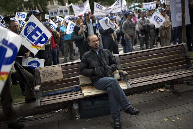 "Rumanian immigrant in Spain Sorin Bedreaga, 38, sits on a bench where he says he has spent 40 days on a hunger strike, as police officers protest by blocking the street in front of the Interior Ministry in Madrid, Spain, Saturday, Oct. 27, 2012. The demonstrators were protesting the government's austerity measures, especially the elimination of their Christmas bonus pay, one of 14 paychecks that most Spanish civil servants get each year. The placard next to Sorin reads in Spanish ""Hunger strike since 17 September 2012"". (AP Photo/Emilio Morenatti)"
