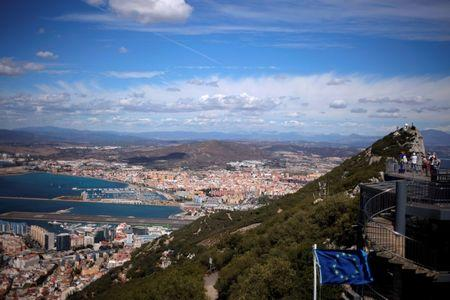 FILE PHOTO: A general view shows the Spanish city of La Linea de la Concepcion and the tarmac of the Gibraltar International Airport while tourists stand on the top of the Rock in the British overseas territory of Gibraltar