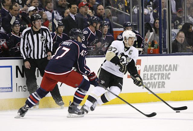 Pittsburgh Penguins' Sidney Crosby (87) keeps the puck away from Columbus Blue Jackets' Dalton Prout (47) during the first period of an NHL hockey game, Friday, March 28, 2014, in Columbus, Ohio. (AP Photo/Mike Munden)