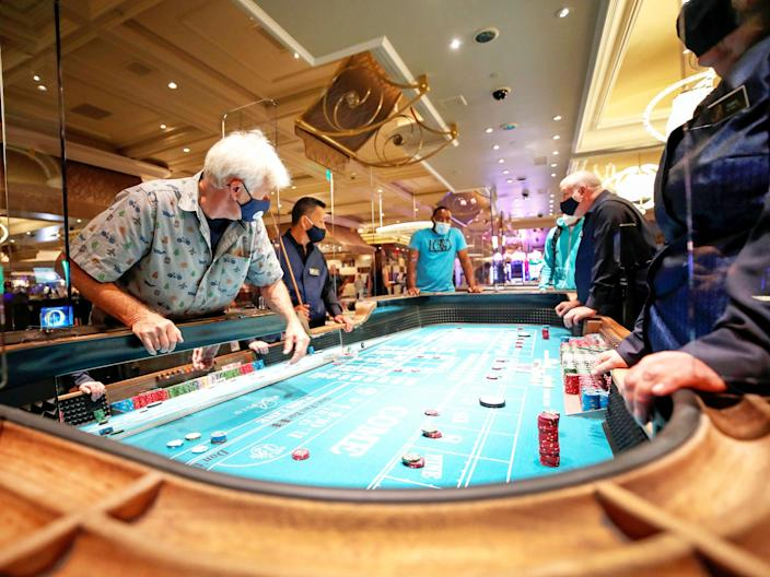A man plays on a craps table fitted with protective plexiglass panels during the reopening of Bellagio hotel-casino in June.