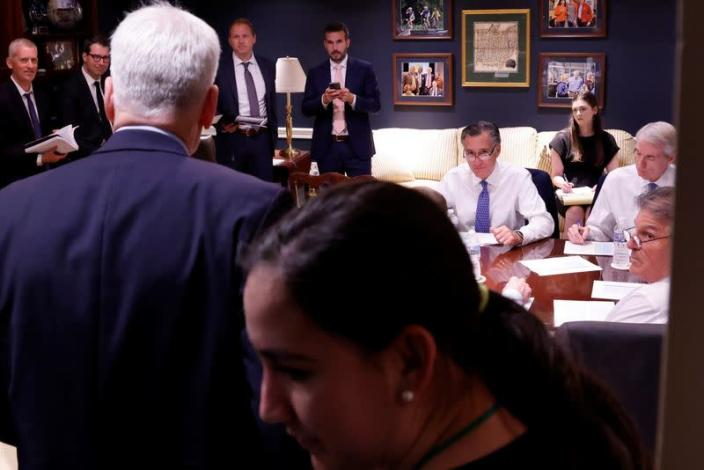 U.S. Senators Romney and Joe Manchin look up as Senator Cassidy arrives at a bipartisan meeting on infrastructure in a hideaway office at the U.S. Capitol in Washington