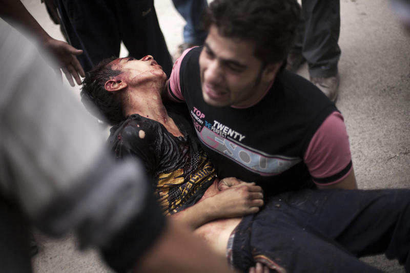 In this Thursday, Oct. 11, 2012 photo, a Syrian man cries while holding the body of his brother, killed by Syrian Army shelling, near Dar al-Shifa hospital in Aleppo, Syria. (AP Photo/Manu Brabo)